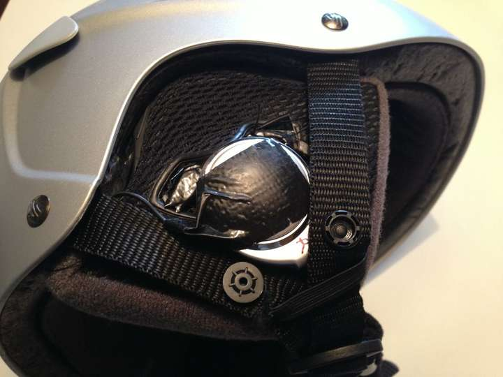 Using duct tape and thread, the headphones are attached to the earflaps of the helmet.